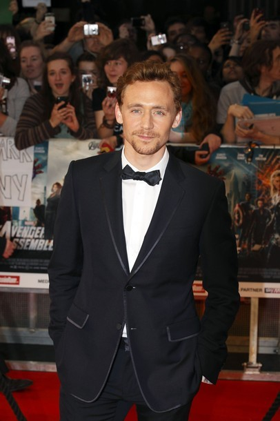 Tom Hiddleston poses for photographs as he arrives for the European premiere of Avengers Assemble at The Vue, Paddington, London, April 19, 2012.