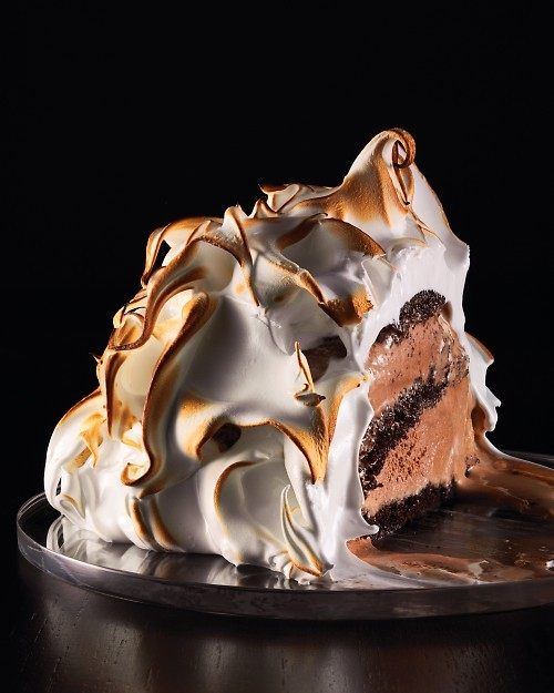cooking-confessions:   Baked Alaska with Chocolate Cake and Chocolate Ice Cream Cake Ingredients:2 cups sugar 1 1/3 cups all-purpose flour 1 cup unsweetened Dutch-process cocoa powder 2 teaspoons baking powder 2 teaspoons baking soda Salt 1 cup vegetable oil 2/3 cup warm water (about 100 degrees) 2 teaspoons pure vanilla extract 6 large eggs, room temperature, separated Assembling Ingredients:Vegetable oil, cooking spray 6 cups chocolate ice cream (3 pints) Meringue Ingredients:12 large egg whites, room temperature 3 cups sugar Pinch of cream of tartar   Directions Preheat oven to 350 degrees. Make the cakes: Sift 1 1/3 cups sugar, the flour, cocoa powder, baking powder, baking soda, and 1 teaspoon salt into a bowl.  Combine oil, water, and vanilla. Whisk egg yolks with a mixer on medium-high speed until pale and thick, about 5 minutes. With machine running, slowly pour oil mixture into yolks, and then add sugar mixture. In a clean mixer bowl, whisk egg whites on medium-high speed, gradually adding remaining 2/3 cup sugar, until medium-stiff peaks form.  Mix one-third of the whites into cake batter, then gently fold in remaining whites. Divide batter between two 12-by-17-inch parchment-lined rimmed baking sheets, and spread evenly using an offset spatula. Bake until cakes are set and spring back when touched, 18 to 20 minutes. Let cool. Assemble the baked Alaska: Coat six 11-ounce bowls or ramekins with cooking spray; line with plastic wrap, leaving an overhang.  Cut out 6 cake circles to fit in bottoms of bowls (we used a 2 1/2-inch round cookie cutter), and place one in each bowl.  Top each with 1/3 cup chocolate ice cream, smoothing surface.  Cut out 6 cake circles to fit on top of ice cream (we used a 3 1/2-inch round cookie cutter), and place on ice cream.  Freeze until set, about 30 minutes. Top each cake with 1/3 cup ice cream, smoothing surface. Cut out 6 cake circles to fit on top of ice cream (we used a 4-inch round cookie cutter), and place on ice cream. (This should fit just at the top of the bowl.)  Cover assembled cakes with plastic wrap overhang, and freeze for at least 4 hours. To remove from bowls, open plastic wrap, flip cakes onto a baking sheet, and remove plastic wrap. Freeze cakes while making meringue. Preheat oven to 500 degrees.  Make the meringue: Heat egg whites, sugar, and cream of tartar in a heatproof bowl of a mixer set over a pan of simmering water, whisking often, until sugar dissolves and mixture is warm to the touch, about 2 minutes.  Transfer bowl to mixer, and whisk until stiff peaks form, about 10 minutes. Cover each assembled cake with 1 cup meringue.  Bake until meringue is browned, 2 to 3 minutes.  Alternatively, hold a small handheld kitchen torch at a 90-degree angle 3 to 4 inches from surface of meringue.  Move flame back and forth until browned and caramelized.