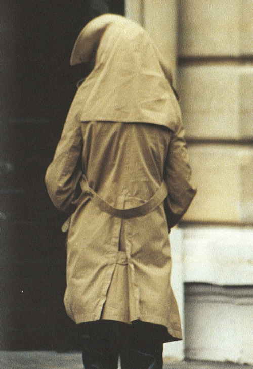 A/W 2005. Photography: Marion Poussier Trench evoked the look of someone sheltering from the rain underneath the coat, collar endings at tip of the head. The neck and shoulder lines were elongated so the coat could be worn as a hood. When not worn up, the coat's collar envelops the shoulders.