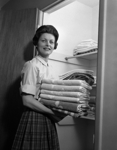1950s housewife holding laundry folded towels by linen closet looking at camera.