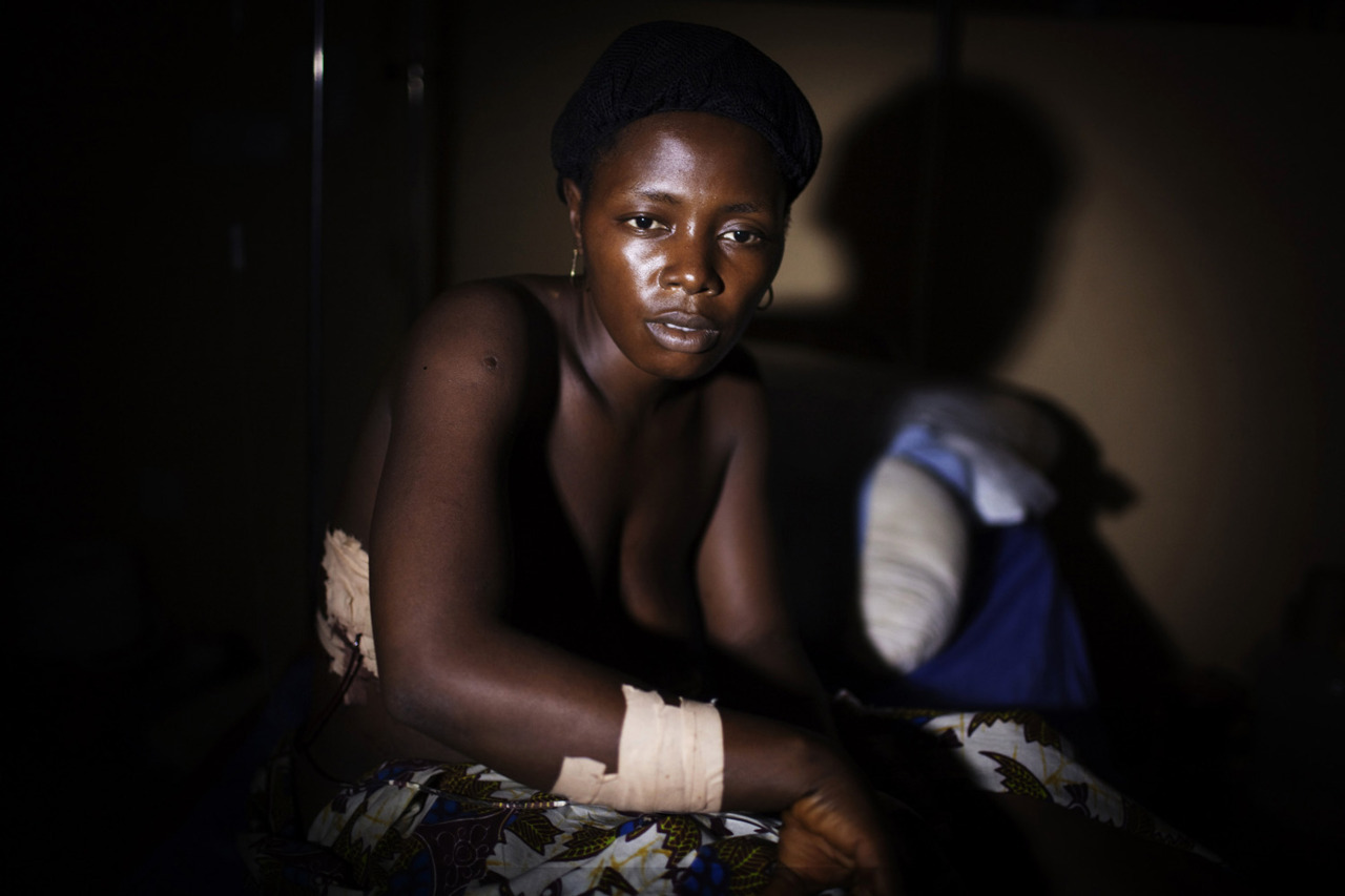 fotojournalismus:  Kadiatu Kauma, 24, sits in hospital with gunshot wounds to her arm, stomach and back after police opened fire on a crowd of protesters in the mining town of Bumbuna April 19, 2012. A woman was shot and killed and several others were wounded when police opened fire on a crowd protesting wages and working conditions at the British mining company African Minerals on Wednesday, according to witnesses, hospital staff and police officials. [Credit : Finbarr O'Reilly/Reuters]
