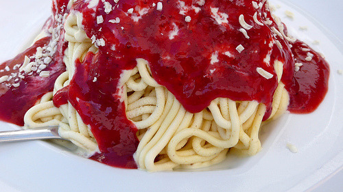 kerwinizer:   Spaghettieisis a German ice cream specialty that looks like a plate of spaghetti. It was invented by Dario Fontanella in the late 1960s in Mannheim, Germany. In the dish, an often light or white colored ice cream is extruded through a modified Spätzle press or potato ricer, giving it the appearance of spaghetti. It is then placed over whipped cream and topped with strawberry sauce (to simulate tomato sauce) and either coconut flakes, grated almonds, or white chocolate shavings to represent the parmesan cheese.  sweet jesus