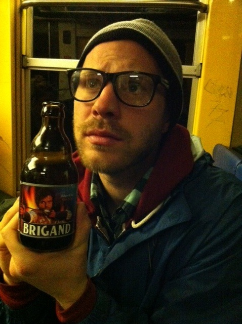 "It's my profound honor to introduce Trainbeer's first foreign correspondent, Dirk VanderHart.  In a recent trip to Europa, VanderHart took Trainbeer to new heights: three trains, three countries, three beverages.  At no point was the intrepid reporter certain this feat was legal, but as he pointed out: ""They speak different languages there, Greg, and I refuse to play that game. Absent any standard signage depicting a martini glass struck tragically through by a teetotaling red line, I assumed a tacit permission to drink and muse."" This is the first in a three-part series.  By Dirk VanderHart Paris, France — RER B line from The Chatelet to Charles de Gaulle AirportBrigand, a Belgian beer, recalls a time when swarthy, illiterate men roamed the forest roads, terrorizing passing caravans of duchesses (presumably wooed after brief bouts in captivity, related to us through a montage showing both parties — ruggedly handsome brigand and fair duchess — gradually letting down their guard and learning, once again, to love). As you can see from the bottle there were fire arrows and shit. Men stood for something greater than mugging for the upcoming election. France being the epicenter of a certain romantic sensibility, and also in the heat of a fiery election year, all this was on my mind as I departed the City of Light for a final hurrah in Spain. It was hot in the train, I remember, and we were seated across from a pair of Irish girls who I guess were about 20. They'd met some Americans in Paris, evidently, and were great fans of the Texas accent. The beer was sweet, in the Belgian style. Also potent (9%) and full. Quite like a large slice of alcoholic wheat cake, if I'm being technical. I drank solemnly, listening to those vapid Irish lilts, swaying with the train car, sweating profusely sans deodorant. Like a Frenchman. No, like a Brigand."