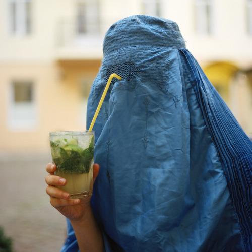 A Muslim woman drinking from her burqa