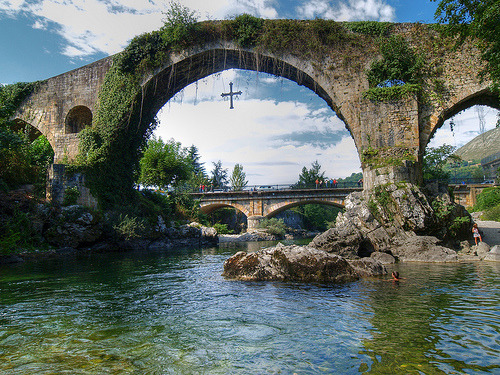 allthingseurope:  Cangas de Onis, Asturias, Spain (by palmeraimperial)  Victory Cross hanging from the bridge, the original is kept in Oviedo's cathedral. The wooden core of this cross is said to haven been carried by King Pelagius in the Battle of Covadonga, were he fought Moors, in the 8th century.  Hahaha sorry for the history lesson. I just love my homeland <3