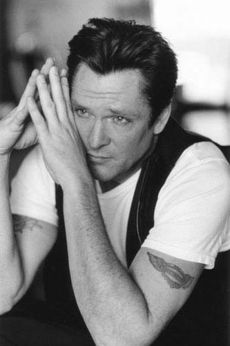 "Top 100 Badass Writers in History #86: Michael Madsen  Born in Chicago, Micharl Madsen was the son of Elaine (Melson), an Emmy-winning poet, television producer and playwright, and Calvin Madsen, a firefighter. Under his parents' instruction, Madsen became interested in the arts at a very young age. He was lucky enough to gain a position at the Steppenwolf Theatre Company in Chicago where he worked as an apprentice to actor John Malkovich. Madsen's 6'2"" stature and husky voice primed him to consistently play the role of tough guys. He is most well known for playing Mr Blonde in Quentin Tarantino's film Reservoir Dogs. The scene where he sadistically slices open a police officer and pours gasoline over him, all to the tune of the cheerful song ""Stuck in the Middle with You,"" has become a cult film classic. To date, Madsen's career spans over 25 years and over 170 films. Some of his biggest box off ice hits include Mulholland Drive, Kill Bill (Vol 1-2), Donnie Brasco, Sin City and Free Willy. His personal aversion to violence and feelings of love and dedication towards his children have influenced the roles that he has taken on in later life, pushing him to move away from the bravado and arrogance of bully characters.  Even among his fans, Madsen is rarely acknowledged for his work as a poet. He has published six poetry collections to this date. His style is often compared to Beat Poetry, making use of the alienation and loneliness that he experiences in daily life. His words find the delicate balance between the rough images he often portrays and the man that he sees behind them, asking such questions as: ""Life is for the living, but death is for the lucky. Why am I a raw nerve? Why must I see the immense sadness in everything?""  In 1998, his book Burning In Paradise won the Independent Firecracker Poetry Award, while in 2010 he was a Guest of Honor at the Crossing Border Festival at The Hague. He has even been awarded the Lifetime Achievement Award for his Complete Poetic Works by Red Hen Press. Madsen continues to work as an actor and has recently made a name for himself as an amateur photography. Although he has recently experienced several scrapes with the law, he remains confident that his artistic work is not yet finished."