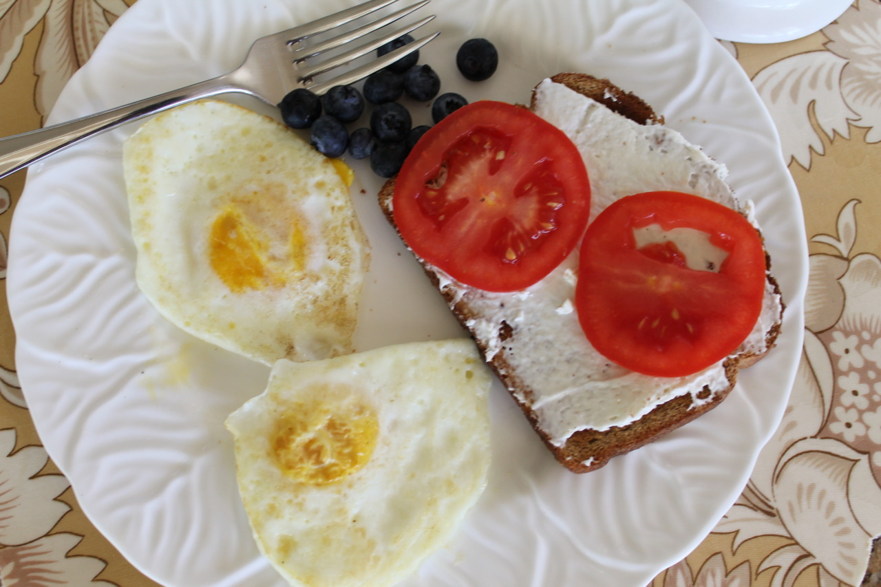 Breakfast! Eggs over medium, wheat toast with cream cheese and tomatoes, and blueberries. Yum.