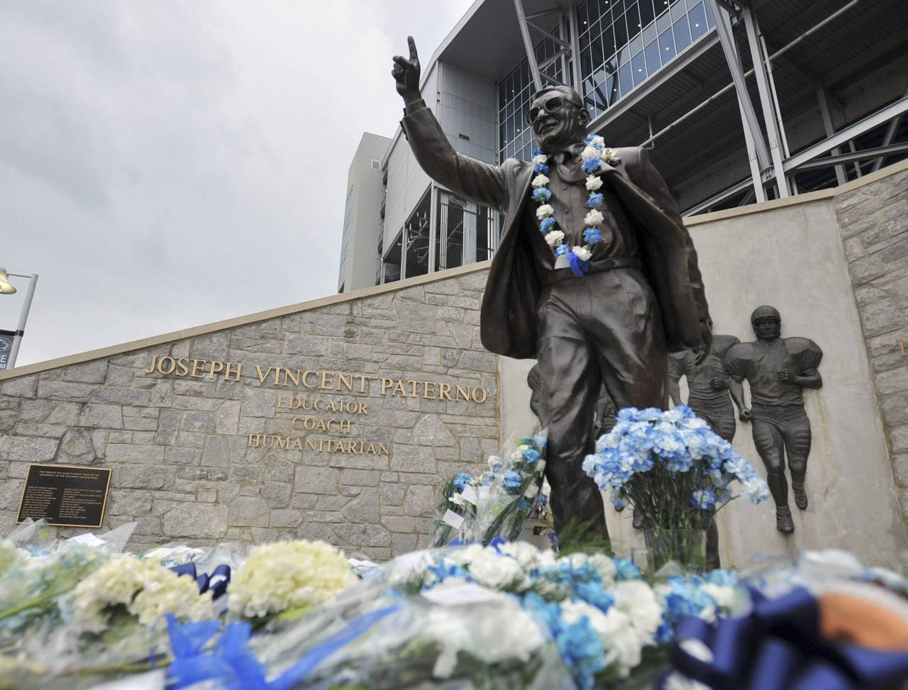 Signs and flowers are seen at the statue of the late Penn State football coach Joe Paterno, before the annual spring football scrimmage in State College, Pennsylvania April 21, 2012. Paterno died on January 22, 2012.Photo: Pat Little/Reuters