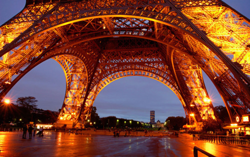The base of the Eiffel tower at dusk. Each night, the tower is lit up, illuminating the Paris skyline.