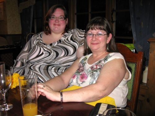 Photo shows me and my mum seated in a restaurant on Friday, while celebrating my grandma's 86th birthday. I'm wearing a grey, black, and white top with a bold wavy pattern and sheer chiffon sleeves, originally from Ann Harvey, and my mum is wearing a cream sleeveless top with a rose print on it. I'm not sure where that's from, sorry. We're both wearing glasses, we both have long dark hair, and we have very similar smiles! Me and my mum, 20th April 2012