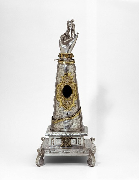 Reliquary from Spain, 1624. From the V&A Museum:  This reliquary once held a fragment of St Scholastica's right arm, visible through the crystal window. A Latin inscription asks the saint to pray for us. Another inscription, as well as the dove perched on her fingers, alludes to Scholastica's death. The holy legend states that her brother St Benedict saw her soul ascending to heaven in the form of a dove.