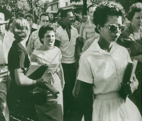 updownsmilefrown:  Elizabeth Eckford of the Little Rock 9 being followed by an angry white mob of students as she is one of the first black students at the school. Hazel Massery (born Bryan,) the one with her mouth open, was never able to escape her participation in this photo, even after many apologies.