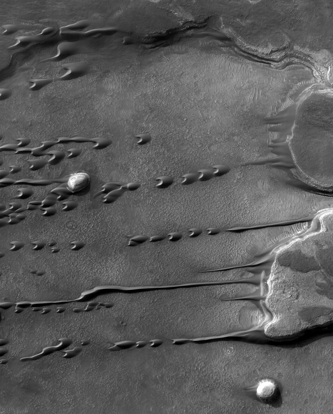 Flowing Barchan sand dunes on Mars, looking like liquid. Although liquids freeze and evaporate quickly into the thin atmosphere of Mars, persistent winds may make large sand dunes appear to flow and even drip like a liquid. Visible on the above image right are two flat top mesas in southern Mars when the season was changing from Spring to Summer. A light dome topped hill is also visible on the far left of the image. As winds blow from right to left, flowing sand on and around the hills leaves picturesque streaks. The dark arc-shaped droplets of fine sand are called barchans, and are the interplanetary cousins of similar Earth-based sand forms. Barchans can move intact a downwind and can even appear to pass through each other. When seasons change, winds on Mars can kick up dust and are monitored to see if they escalate into another of Mars' famous planet-scale sand storms.