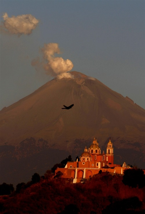 newsflick:  A plume of ash and steam rise from the Popocatepetl volcano overshadowing the Catholic church 'Nuestra Señora de los Remedios' or 'Our Lady of Remedies' in Cholula, Mexico, April 22. [Marco Ugarte / AP via MSNBC]