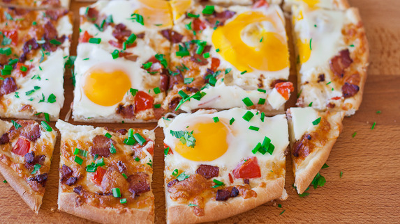 justbesplendid:  Breakfast pizza by JoCooks Ingredients: 1/3 pizza dough (recipe here) 1 cup mozzarella cheese 1/4 cup Parmesan cheese, freshly grated 1 tomato, chopped in small pieces 4 slices of bacon, cooked and cut into small pieces 4 eggs chives and parsley for garnish Directions: Preheat oven to 500 F degrees. Spray the pizza baking dish with cooking spray. Roll out the pizza dough and place it on the pizza baking dish. Arrange the mozzarella cheese evenly over the dough. Add the Parmesan cheese. Add the bacon and tomatoes to the pizza, making sure they're spread evenly over the pizza. Crack 4 eggs on the pizza and bake for 10 to 15 minutes. Garnish with chives and parsley.