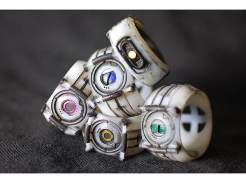 "otlgaming:  ROBOTIC RINGS Our favorite robots straight from Aperture Laboratories can now be worn with any outfit. It also transform the question of ""Did he put a ring on it?"" to the gamer version, ""Did he put a Wheatley ring on it?"" Portal Robot Rings by Ammnra via Shapeways (via pwnlove)  Been posting a lot of portal jewellery lately. but my god I do want one!"