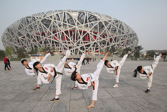 Chinese young athletes practice Taekwondo techniques before the rehearsal of ceremony to mark 100-day countdown to London 2012 Olympic Games in Beijing last Tuesday. (Feng Li/Getty Images)