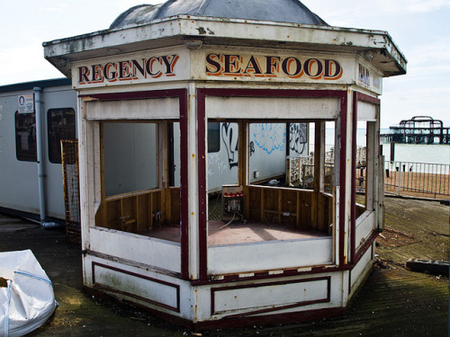 Regency Seafood Bar opposite the West Pier, Brighton on Flickr.The Regency Seafood Bar (opposite the West Pier, Brighton) has seen better days. The whole area that was originally part of the entrance to the West Pier is being demolished This is all part of plans to build the i360. This news item was published on 17th April 2012 on the West Pier website: The West Pier Trust wishes to announce that an important original part of the pier, the Rock Shop, will be dismantled over the next few weeks. Situated on the root end of the pier, the Rock Shop was closed three years ago when it became structurally unstable. Its condition has continued to deteriorate and so the Trust and its partners, Marks Barfield Architects, designers of the i360, have decided it is time carefully to dismantle it and put it into safe storage. Since the restoration of this building is part of the i360 scheme, Marks Barfield are bearing the cost of the work. In due course it will be restored and reinstated, along with a replica of its sister kiosk on the west side of the pier's root end, as one of the heritage elements of the i360. In fact it will be reopened as a toll booth which was its purpose when the pier opened originally in 1866. The dismantling work will be carried out by Dorton Group and overseen by the Trust's consultant engineers, Hemsley Orrell Partnership. As part of the work, the pier's root end will also be improved. The two 1990s kiosks which are no longer used will be removed, the hoarding realigned and the Heras fencing replaced. Popular views of the pier will not be obstructed but, we hope, improved. No firm timetable has been announced for the i360 development but architects and designers of the scheme, Marks Barfield are continuing to seek the final balance of funding. Once all the financial backing is in place work will start within weeks.