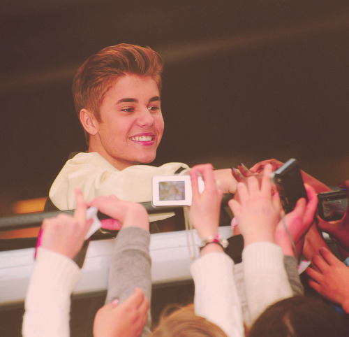 Justin Bieber greeting fans while leaving his hotel in London. (photos)