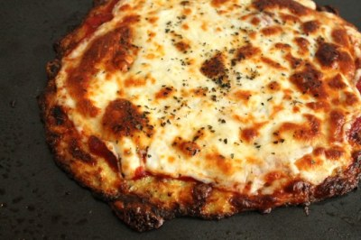 overcoming-obstacles:  Cauliflower Crust Pizza Ingredients: (1 serving)1 cup cooked, riced cauliflower1 cup shredded mozzarella cheese1 egg, beaten1 tsp dried oregano1/2 tsp crushed garlic1/2 tsp garlic saltOlive oil (optional) Pizza sauceMozzarella cheese, shreddedOther additional toppings of your choice Directions:To rice your cauliflower, take 1 large head of cauliflower, remove the stems and leaves, and chop the florets into chunks. Add to a food processor and pulse just until it looks like rice. Alternatively, you can grate the cauliflower with a cheese grater. Place the riced cauliflower in a microwave safe bowl, add 1/4 cup water, and microwave for 6-8 minutes, stirring half-way through. To make the pizza, preheat the oven to 450 degrees F. Spray a pizza pan or cookie sheet with non-stick cooking spray. In a medium bowl, combine the cauliflower, mozzarella cheese and egg together and stir until well incorporated. Add the oregano, garlic, and garlic salt. Transfer to the cookie sheet, and shape into a 9-inch circle. Brush the crust with olive oil to help it brown in the oven. Baked at 450 degrees F for 15 minutes, until the crust is browned and cooked through the middle. Remove the crust from the oven, add your sauce and toppings. Place under a broiler at high heat until the cheese is melted and bubbly. (About 3-4 minutes). Allow the pizza to cool slightly, then cut into slices and serve.