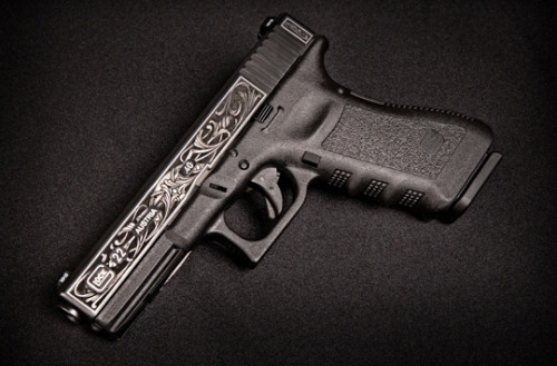 gunrunnerhell:  Custom Glock 22 (You either love or hate the Glock series of pistol but for what they're worth, its one of the best semi-auto handguns out there. I did a post a while back on engraving; it can be done well or be absolute crap. I actually kind of like how this Glock looks though I'd probably keep it a safe queen.)