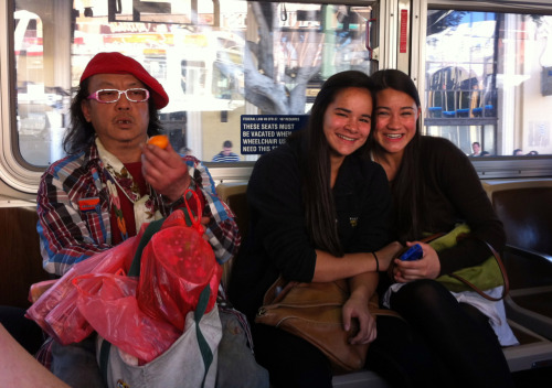 "San Francisco is a Wonderland and these girls (""half-Chinese, duh"" -their older sister and photographer) are like twin Alices in the moment of meeting the Caterpillar. In his hand he holds a Mandarin orange, not to eat or to consider, but as an extension of his person. Part Buddha, part explosion at a craft store, our sloppy mystic exists on a higher, slightly uneven plane that we only mistakenly perceive to be a city bus on the Chinatown route. He could be the nephew of the Best Dressed Man in the World. I see the same flair for color layering, hopefully a strong genetic trait, with a bit still to be desired in the presentation department. Although, to his credit as an individual, somewhere in there appears to be a necklace made of potholder loops. Even hipsters of the most iron constitutions might not have that kind of courage.    Photos by Catherine Beadles, March 2012."