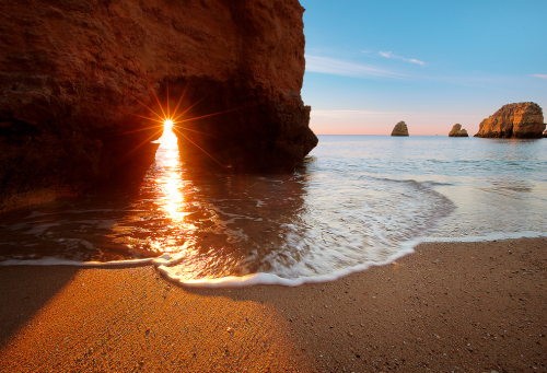 ecocides:  Sunrise on a Lagos beach, Portugal | image by lichtmaedel