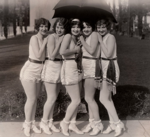 "clarabowarchive:  Five Flappers, One Umbrella ☆ Clara Bow (age 22) ☆ Rough House Rosie (1927) ☆ Original caption typed on reverse:  CLARA BOW & DANCING GIRLS LOS ANGELES - - - - - - - Now let it rain! - - - Clara Bow and four of the dancing girls in her newest picture for Paramount, ""Rough House Rosie,"" make up for an inadequate umbrella by braving a threatening shower in their dancing costumes. 2/4/27"