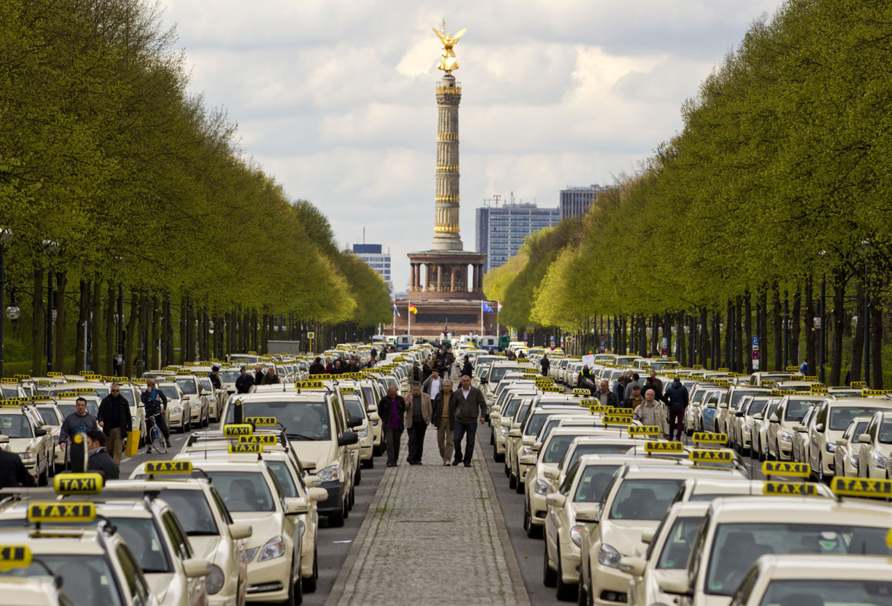 Taxis line the Strasse des 17. Juni thoroughfare in central Berlin during a strike by taxi drivers against new tariffs for journeys to and from Berlin's new international airport, April 23, 2012. In background is the Siegessaeule (victory column). REUTERS/Thomas Peter