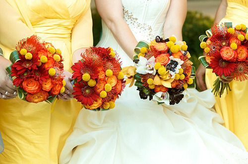Bright yellow and orange bouquets, with gerbera, orchids, roses and protea.