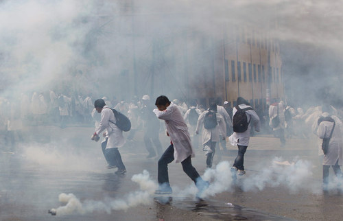 Medical students run away from tear gas in La Paz, Bolivia. The students had been holding a demonstration in support of public doctors on strike Photograph: Juan Karita/AP