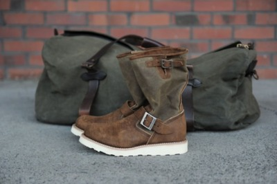 Filson Duffle Bag and Red Wing Limited Engineer Boots - REDWING1905 The Engineer collection was originally developed for engineers working on America's railroads. The boots with pull-on styling, used minimal stitching to protect the engineer's feet from the hot embers that fell from the locomotive's firebox. The buckled side gusset at the top of the boot allowed for easier bending, a necessary requirement as they needed to continuously shovel more coal into the firebox. The first engineer boots, number 919, appeared in the 1941 catalog—they were advertised as pull-on boots for engineers and truck drivers, the new engineers of the open road.