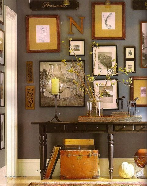 Don't be afraid to mix colors and styles in a wall grouping. Here, the sharp black and whites blend with the wall and woodwork colors, while the earth tone frames and mats coordinate with other accessories in the vignette.
