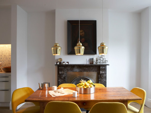 Bright Rooms: Warm GlowA trio of shiny brass pendant lights and bright lemon yellow chairs add elements of chic to neutral dining table. Get more bright ideas here.