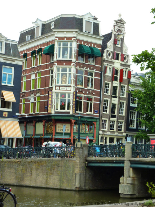 The Leaning Buildings of Amsterdam  I love how wonky the buildings are in Amsterdam :-) Look at the way the gap between the Chinese emporium and the building to its right (dated 1644) increases. I'd love to look inside one of these houses to see if they're just as wonky inside.  Because landspace was limited, many buildings were built very tall and very narrow. The sideways leaning is due to the weight of the heavy brick structures bearing down on wooden piles that are buried deep into the mud and sand below.  Do you also see the beams sticking out at the very top of the buildings? Their purpose is to hold a hook so that furniture can be hoisted up from the ground and brought in through the windows. The internal stairs are far too steep and narrow to bring furniture in that way! Apparently, the houses also lean forward a bit too, to make the job of hoisting easier.     Well now you know :-)