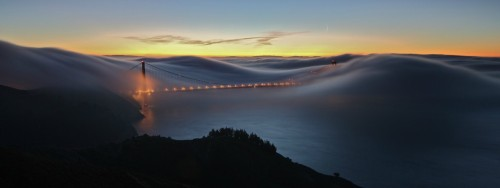 What could be the Golden Gate Bridge, is covered in fog which looks strikingly similar to waves. The photo was most likely taken in the early morning, when the fog is still rolling in from the ocean.