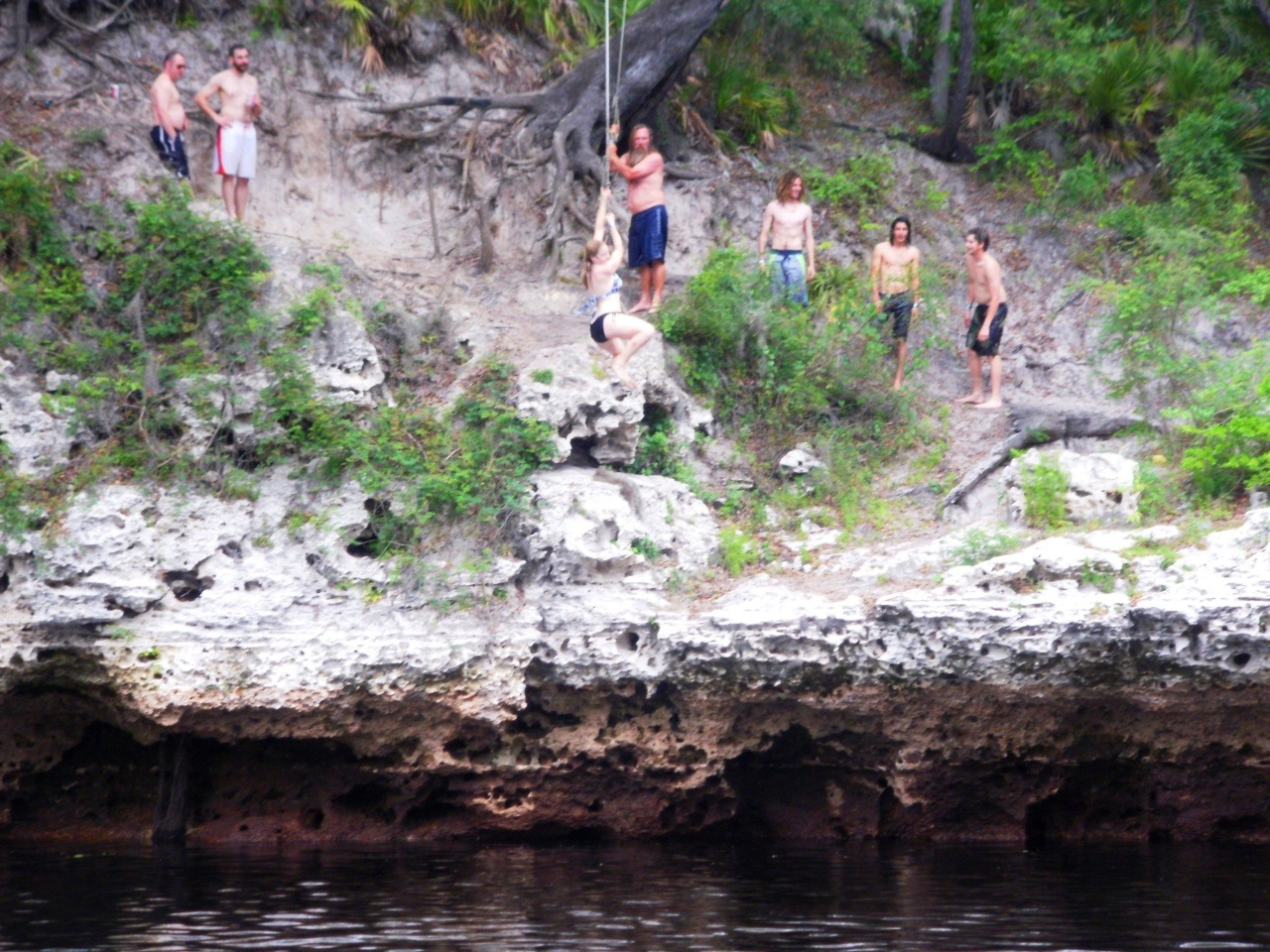 Swinging off a cliff from a rope into the black river at Live Oak, FL