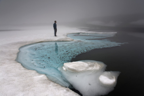 In the words of photographer Andri Elfarsson: Iceland  A mystical place, Iceland. Shot in June. This image is shot standing on melting ice over Bræðravatn, Mjóafjarðarheiði. The locals tell me this is never to be done again. The name, Lake of Brothers, comes from two brothers who drowned in the extremely deep and cold water after the ice broke.