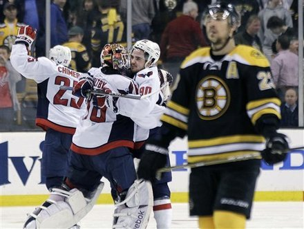 Boston Bruins center Chris Kelly (23) skates away as Washington Capitals goalie Braden Holtby (70); center Marcus Johansson (90), of Sweden; and left wing Jason Chimera (25) celebrate the Capitals' 2-1 win in overtime in Game 7 of an NHL hockey Stanley Cup first-round playoff series, in Boston on Wednesday, April 25, 2012.