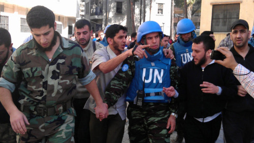 "U.N. Monitors Fail To Halt Violence In Syria The U.N.-brokered cease-fire in Syria keeps unraveling. Syrian government troops were supposed to pull their tanks and soldiers out of cities and towns, while rebels were supposed to lay down their arms. Yet hundreds of people have died in recent days, according to activists. And in some areas, visits by U.N. observers have been followed by intense violence. Only about a dozen U.N. observers have reached Syria. Wearing their signature U.N.-blue berets or helmets, their goal is to see whether government troops and rebels are sticking to the cease-fire, which went into effect April 12. In some places, like the flashpoint city of Homs, the mere presence of monitors does seem to be stemming the violence. Fighting In Hama But in other locations, like the central city of Hama, it's not so simple. Videos taken by Hama residents and posted on the Internet show people holding olive branches, crowding around the U.N. monitors' vans, begging for help with detained relatives or destroyed homes. ""Bashar al-Assad kills us,"" one man says, referring to the Syrian president. ""We want freedom."" After the monitors left, the protests continued. Activists say snipers posted on rooftops opened fire — a fairly common occurrence these days in Syria. To go out and protest is to risk being injured or killed. Pictured: Members of the Syrian opposition walk with a U.N. observer during a visit by monitors to the restive city of Homs, Syria, on April 21. Opposition activists say observers appear to help bring calm if they stay in an area. Two monitors have been deployed in Homs for the past several days."