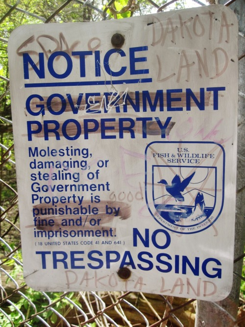 NO TRESPASSING - DAKOTA LAND laishe:  This was taken at the Minnehaha off-leash dog park in Minneapolis that sits on sacred Dakota land. This sign is off the trail close to Coldwater Spring.  O, MY MY!