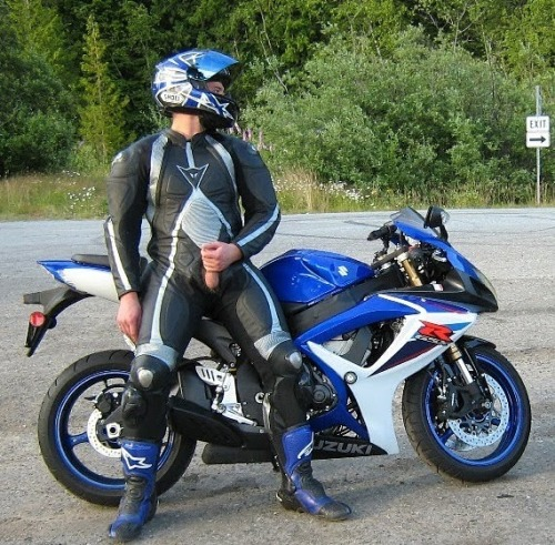 Motorcyclist in a suit, masturbating beside his racing bike roadside.