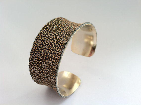 Gold Real Stingray Leather Cuff Bracelet This is Stunning Real Stingray leather lined with a beautiful Gold plated cuff. This Bracelet sparkles like diamonds on your wrist. The leather is dyed a beautiful golden color that picks up other colors around that add that Gorgeous sparkle. This Cuff Bracelet is just over 1 inch wide and fits size 5.5- 8 inches with a gentle closing and opening. I also have the 2 inch wide cuff in my shop if you prefer a bolder look. Thank you for looking!Stormy $65.00