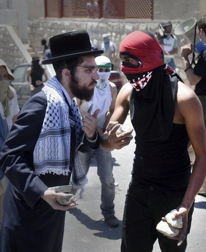 paxamericana:  machistado:  thomcurse:  When orthodox Jews joined with Palestinian youths throwing stones at Israeli police  This is pretty surreal. Is there a source for this? I'd love some more context.   A member of Neturei Karta, a fringe of the ultra-Orthodox movement within the anti-Zionist bloc in Israel, talks with a masked Palestinian youth as he shows his support during clashes with Israeli police in the mostly Arab neighborhood of Silwan in Jerusalem. Palestinian protesters clashed with Israeli police as dozens of ultra-nationalist Jews carried Israeli flags through Silwan to assert Jewish sovereignty over all of Jerusalem, according to the organizers of the march.