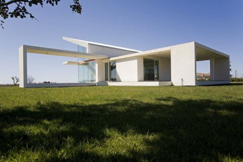 Design team: ARCHITREND Architecture villa_tumino_2008  Location: Ragusa Italy The relationship with the context and the sequence of the three stacked floors relies on a sort of continuous architectural ribbon that reinterprets the flavor of the Mediterranean home, developing, bending to form rooms and the roof, outdoor zones raised from the meadow like platforms, porticos and overhangs, balconies and terraces. A solid facade clad in stone, to the north, is flanked by the harmonious antithesis of the southern and eastern facades, fully glazed and open to the greenery. The white stucco and stone facings that wrap the forceful geometric design, highlighted by a red floor marker that interrupts the high corner glazing, the planes that combine, in a dynamic way, around the sloping roof, reveal the pursuit of a 'possible Mediterranean style' that pays attention to local history, but without copying, ready for experimentation with new possibilities.