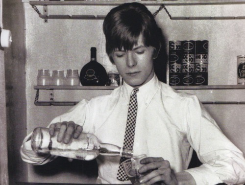 David Bowie pours a drink.