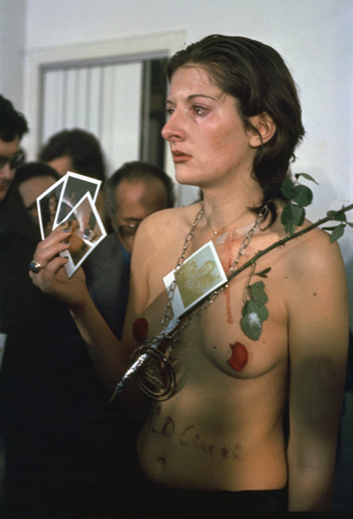 "Rhythm 0 (1974) by Marina Abramovic To test the limits of the relationship between performer and audience, Abramović developed one of her most challenging (and best-known) performances. She assigned a passive role to herself, with the public being the force which would act on her.Abramović had placed upon a table 72 objects that people were allowed to use (a sign informed them) in any way that they chose. Some of these were objects that could give pleasure, while others could be wielded to inflict pain, or to harm her. Among them were scissors, a knife, honey, a rose, a whip, and, most notoriously, a gun and a single bullet. For six hours the artist allowed the audience members to manipulate her body and actions.Initially, members of the audience reacted with caution and modesty, but as time passed (and the artist remained impassive) several people began to act quite aggressively. As Abramović described it later: ""What I learned was that…if you leave it up to the audience, they can kill you."" … ""I felt really violated: they cut up my clothes, stuck rose thorns in my stomach, one person aimed the gun at my head, and another took it away. It created an aggressive atmosphere. After exactly 6 hours, as planned, I stood up and started walking toward the audience. Everyone ran away, to escape an actual confrontation."""