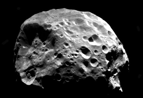 "Saturn's Moon Phoebe has Interesting Origins More than 60 moons are known to orbit Saturn, varying drastically in shape, size, surface age and origin. Scientists had their first close-up look at Phoebe when Cassini began exploring the Saturn system in 2004. Using data from multiple spacecraft instruments and a computer model of the moon's chemistry, geophysics and geology, scientists found Phoebe was a so-called planetesimal, or remnant planetary building block.    Phoebe was born within the first 3 million years of the birth of the solar system, which occurred 4.5 billion years ago. The moon may originally have been porous but appears to have collapsed in on itself as it warmed up. Phoebe developed a density 40 percent higher than the average inner Saturnian moon.  Cassini images suggest Phoebe originated in the far-off Kuiper Belt, the region of ancient, icy, rocky bodies beyond Neptune's orbit. Data show Phoebe was spherical and hot early in its history, and has denser rock-rich material concentrated near its center. Its average density is about the same as Pluto, another object in the Kuiper Belt. Phoebe likely was captured by Saturn's gravity when it somehow got close to the giant planet.                         Objects like Phoebe are thought to have condensed very quickly. Hence, they represent building blocks of planets. Saturn is surrounded by a cloud of irregular moons that circle the planet in orbits tilted from Saturn's orbit around the sun, the so-called equatorial plane. Phoebe is the largest of these irregular moons and also has the distinction of orbiting backward in relation to the other moons. Saturn's large moons appear to have formed from gas and dust orbiting in the planet's equatorial plane. These moons currently orbit Saturn in that same plane.  Objects of Phoebe's size have long been thought to form as ""potato-shaped"" bodies and remained that way over their lifetimes. If such an object formed early enough in the solar system's history, it could have harbored the kinds of radioactive material that would produce substantial heat over a short timescale. This would warm the interior and reshape the moon.  Phoebe likely stayed warm for tens of millions of years before freezing up. The study suggests the heat also would have enabled the moon to host liquid water at one time. This could explain the signature of water-rich material on Phoebe's surface previously detected by Cassini.   The new study also is consistent with the idea that several hundred million years after Phoebe cooled, the moon drifted toward the inner solar system in a solar-system-wide rearrangement. Phoebe was large enough to survive this turbulence."