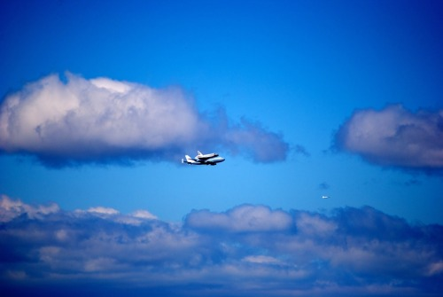 carrotcreative:  Space shuttle Enterprise was placed on top of the NASA 747 Shuttle Carrier Aircraft at Dulles Airport on April 20. We captured some shots from our view at 45 Main St in Brooklyn! photo credit: Tom Milewski for Carrot  That's a space ship, on a plane, flying around lower Manhattan.
