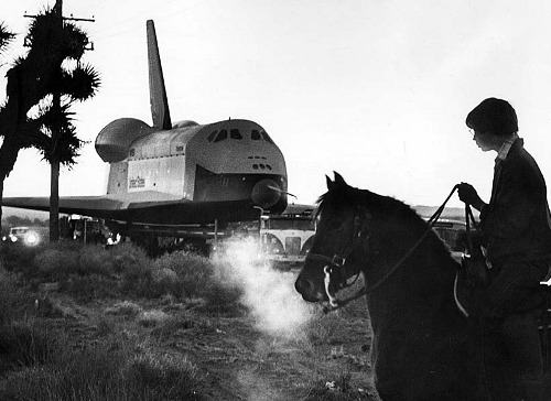 """Jan. 31, 1977: A horse and rider watch as the space shuttle Enterprise is towed from a Rockwell International facility in Palmdale to Edwards Air Force Base for a year of flight tests. Townspeople lined the route for a glimpse of the 110-ton shuttle. A 90-wheel transport was used and accompanied by a 20-vehicle convoy."" (via)"
